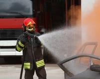 Il pompiere con il casco fuori dall'automobile ha bruciato con la schiuma Fotografia Stock