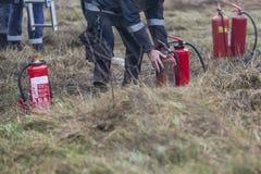 Il pompiere controlla gli estintori durante addestramento e la pratica fotografia stock libera da diritti
