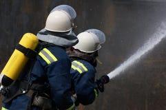 Il pompiere estingue il fuoco Fotografie Stock