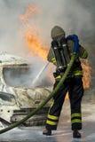 Il pompiere estingue il fuoco dell'automobile Immagini Stock Libere da Diritti