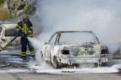 Il pompiere estingue il fuoco dell'automobile Fotografia Stock