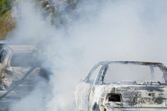 Il pompiere estingue il fuoco dell'automobile Immagine Stock