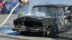 Il pompiere Fire Brigade dispensa la schiuma sull'automobile bruciante durante il trapano video d archivio