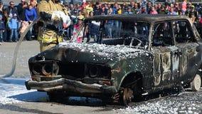 Il pompiere Fire Brigade dispensa la schiuma sull'automobile bruciante durante il trapano stock footage