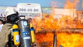 Il pompiere Fire Brigade dispensa la schiuma sull'automobile bruciante durante il trapano archivi video