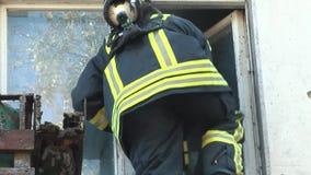 Il pompiere scala una finestra dell'appartamento per conservare la gente E video d archivio