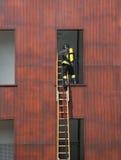 Il pompiere sulla scala di legno entra nella finestra Immagine Stock Libera da Diritti