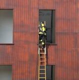 Il pompiere sulla scala di legno registra la finestra nel fuoco s Fotografie Stock