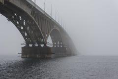 Il ponte attraverso il fiume nella nebbia Vista da sotto il ponte dell'arco al fiume Fotografie Stock
