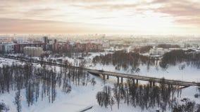 Il ponte attraverso l'inverno del fiume Portata sopra la città con un uccello antenna 4k Sopra il fiume ed il ponte congelati del archivi video