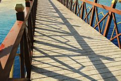 Il ponte sopra il fiume in un cielo blu di legno della ferrovia del pavimento di calcestruzzo del parco riflette giù il fiume immagine stock libera da diritti