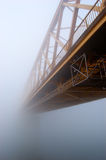 Il ponticello giallo sparisce nella nebbia spessa di autunno Fotografia Stock