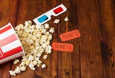 Il popcorn è stato sparso dalla scatola, dai vetri 3D e dal ticke di film Fotografia Stock