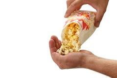 Il popcorn ha versato in una mano Fotografia Stock
