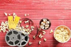 Il popcorn, i biglietti ed il film saporiti annaspano su fondo rosso Fotografia Stock Libera da Diritti