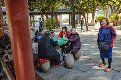 Il popolo cinese senior ha lasciato per rilassarsi e giocare la carta nel parco ancestrale del tempio Porcellana della città di F immagine stock libera da diritti