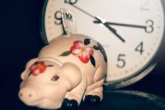 Il porcellino salvadanaio con contanti sui precedenti dell'orologio, Il tempo è denaro, Immagini Stock