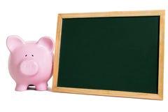 Il porcellino salvadanaio con la piccola lavagna in bianco, risparmio di istruzione scolastica costituisce un fondo per il concet Immagine Stock