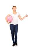 Il porcellino salvadanaio felice e la rappresentazione della tenuta della giovane donna sfogliano su Fotografia Stock