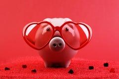 Il porcellino salvadanaio innamorato con gli occhiali da sole rossi del cuore che stanno sulla sabbia rossa con cuore brillante r Immagine Stock