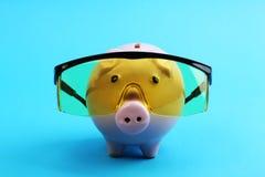 Il porcellino salvadanaio rosa con i vetri gialli su fondo blu gradisce lo scienziato Fotografia Stock