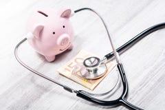 Il porcellino salvadanaio rosa esamina una banconota dell'euro 50 con uno stetoscopio - controllare il concetto di situazione fin fotografia stock