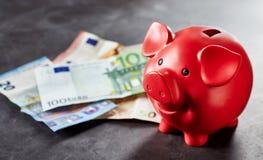 Il porcellino salvadanaio rosso e le euro banconote su gray sorgono Immagine Stock