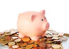 Il porcellino salvadanaio sta stando in un'area dalle euro monete Fotografia Stock Libera da Diritti