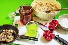 Il porridge, melograno, miele, ha arrostito il dado, yogurt, bevanda di vera dell'aloe Immagini Stock