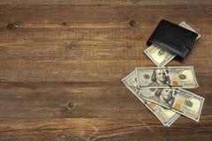 Il portafoglio degli uomini con i contanti del dollaro sui precedenti di legno approssimativi Fotografia Stock