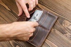 Il portafoglio dell'uomo di Brown in mani dell'uomo Immagine Stock