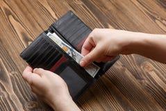 Il portafoglio dell'uomo di colore in mani dell'uomo Fotografia Stock