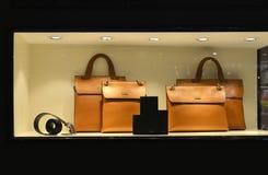 Il portafoglio di cuoio di lusso della cinghia della borsa nella finestra del negozio si è acceso dalle luci principali Fotografia Stock