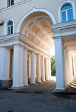 Il portale incurvato con le colonne che conducono nel cortile Immagine Stock