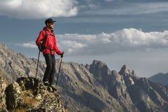 Il portatore dei pantaloni a vita bassa barbuti del viaggiatore in occhiali da sole e di un cappuccio con uno zaino ed i pali di  fotografia stock