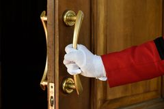 Il portiere apre le mani della porta dell'hotel in guanti bianchi immagini stock libere da diritti
