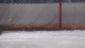 Il portiere dell'hockey pulisce i pattini da ghiaccio davanti al portone che prepara per il gioco stock footage