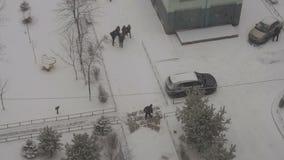 Il portiere With Snow Shovel sta pulendo un percorso Scolari che camminano giù la via archivi video