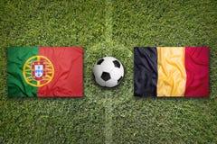 Il Portogallo contro Bandiere del Belgio sul campo di calcio Fotografia Stock Libera da Diritti
