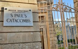 Il portone chiuso dell'entrata con il segno alle catacombe ed al museo di St Paul su una parete dell'arenaria immagini stock libere da diritti