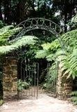 Il portone di giardino del metallo con l'arco ha messo in recinto del mattone Immagini Stock