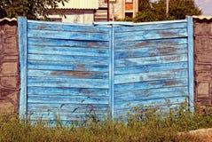Il portone e la parte di legno blu di una pietra recintano l'erba Immagini Stock