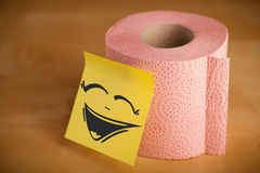 Il Post-it con il fronte sorridente sticked sulla carta igienica Fotografia Stock