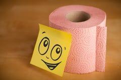 Il Post-it con il fronte sorridente sticked sulla carta igienica Immagini Stock