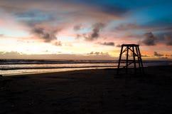 Il posto di guardia del bagnino in siluetta in un'alba in una spiaggia con il sole colora il cielo della pittura fotografia stock