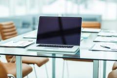 il posto di lavoro con il computer portatile aperto ed i documenti finanziari hanno preparato per la riunione dei soci commercial Immagine Stock Libera da Diritti