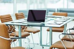 il posto di lavoro con il computer portatile aperto ed i documenti finanziari hanno preparato per la riunione dei soci commercial Immagine Stock