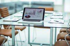 il posto di lavoro con il computer portatile aperto ed i documenti finanziari hanno preparato per la riunione dei soci commercial Fotografia Stock