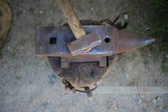 Il posto di lavoro del ` s del fabbro è un martello e un'incudine immagini stock