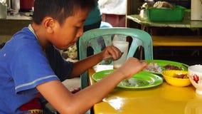 Il povero boyl mangia con la mano pulita sulla tavola stock footage